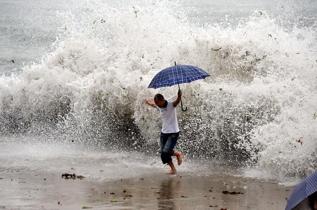 图为被海浪袭击的游客. 2/77月12日,青岛.