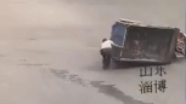 三轮车闯红灯被撞侧翻 路人合力抬起后发生哭笑不得一幕