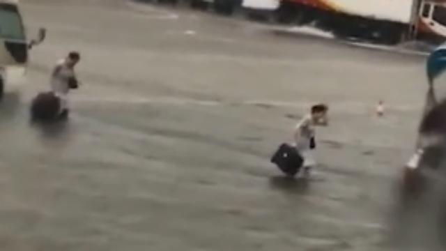 海南海口:美兰机场机坪被淹 空姐趟水上飞机