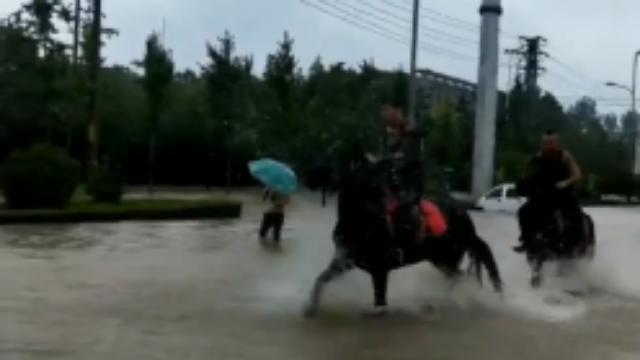 商丘暴雨街道开启看海模式 男子雨中骑马踏浪前行