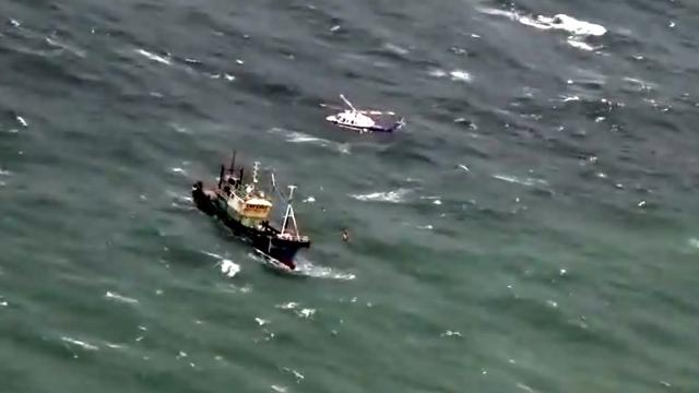 实拍:渔船遇险随海浪浮沉 渔民亟待救援 直升机悬停空中救助