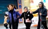 女儿带盲人父母逛街 三人搭肩而行