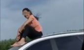 女子贪玩坐车顶吹风 被罚10元