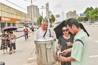 """公交站旁摆""""免费茶水点"""" 路人可自取饮用"""