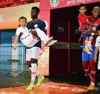 暖心!暴雨致场地大量积水 球员抱球童入场
