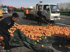 陕西咸阳:1.5吨苹果散落路面 警察帮捡拾
