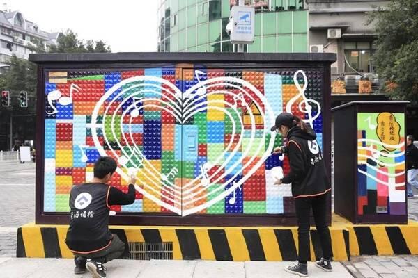 """龙凤桥街道龙凤路,两名手绘爱好者在给配电箱""""涂鸦"""""""