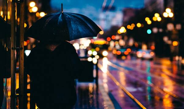 person walking on street while holding black umbrella near cars on road at nighttime