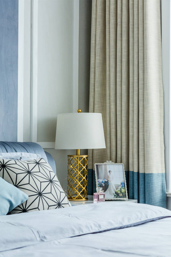 主卧的床头是边框造型,中间大面积的灰蓝色,再挂一幅婚纱照,结合现代