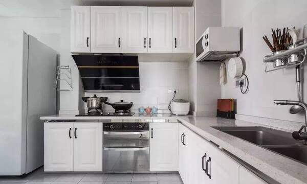 厨房地面通铺灰色瓷砖,立面浅色瓷砖搭配白色橱柜,灰色麻点台面耐脏