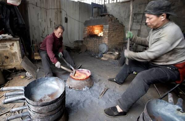 煅烧炉前,两位铁匠不断将炉里烧红的铁板取出,放在铁墩上,一锤锤打出