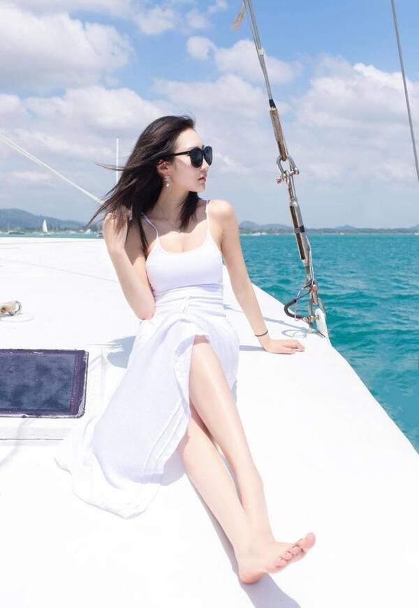 游艇上白皙性感的吹风美女,海上风景无限美