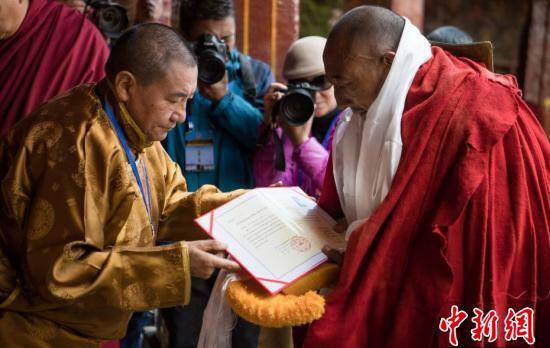 4月13日,中国佛教协会西藏分会会长、西藏佛学院院长珠康·土登克珠活佛(左)向考僧颁发格西拉让巴学位证书。当日,在拉萨大昭寺大殿举行西藏自治区2018年度藏传佛教学经僧人考核晋升格西拉让巴学位立宗答辩暨颁证仪式。来自拉萨色拉寺、哲蚌寺等寺庙的9名考僧参加了立宗答辩,晋升格西拉让巴学位。该学位是藏传佛教格鲁派僧人修学显宗的最高学位。中新社记者 何蓬磊 摄