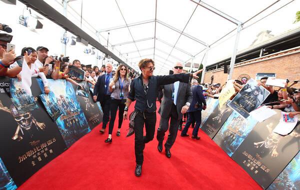 """5月11日,电影《加勒比海盗5》在上海迪士尼举行全球首映礼,主演约翰尼·德普、奥兰多·布鲁姆、杰弗里·拉什、哈维尔·巴登等电影主创空降上海,和影迷亲密互动。德普叔在红毯彻底""""燃""""起,给粉丝签名签嗨了,甚至舍不得走,最后被保镖""""强行""""架走。图为约翰尼·德普。"""