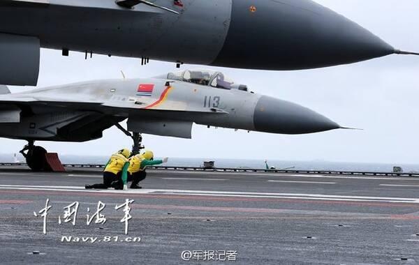 """2日上午9时30分许,随着起飞助理郭晖和战友标准的放飞手势,歼-15舰载战斗机滑跃起飞,冲向云层低垂的天空,中国南海上空首次迎来""""飞鲨""""身影。自此,歼-15舰载机实现在中国四大海域起降航母!"""