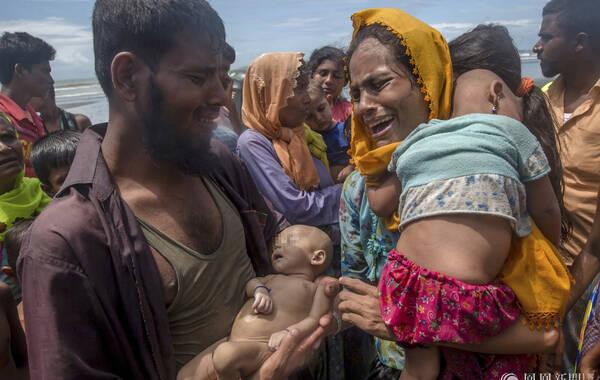 当地时间2017年9月14日,孟加拉国Shah Porir Dwip,缅甸罗兴亚难民乘船抵达孟加拉海湾,他们搭载的小船发生了倾覆。一名男子抱着自己溺亡的幼儿,妻子崩溃大哭。为逃避缅甸西北部若开邦暴力冲突,缅甸罗兴亚人近三周来大量涌入孟加拉国,寻求帮助和安全之地。