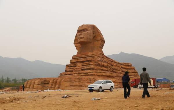 """按照1:1仿造的""""埃及狮身人面像""""坐落于河北省石家庄市山前大道旁洞沟村东的一片空地上,坐北朝南紧邻太行山脉,身长约60米,身高约20米,正面以及两侧面有小门可以进去。""""这倒省去了出国的飞机票钱"""",一男游客开玩笑的说到。图为山寨""""狮身人面像""""。"""