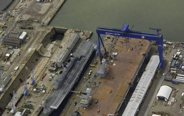 """随着英国皇家海军最新型的伊丽莎白女王级航母首舰""""伊丽莎白女王""""号下水时刻的临近,这艘英国有史以来建造的最大水面战舰已经做好了准备。从最新公布的图片可以看到,""""伊丽莎白女王""""号航母的甲板已经基本清空,在滑跃甲板前端也摆放了一架F-35战斗机的模型。同时,英国皇家海军现役的""""卓越""""号航空母舰也在厂区内并列停靠,共同参加""""伊丽莎白女王""""号航母的下水盛典。(环球网)"""
