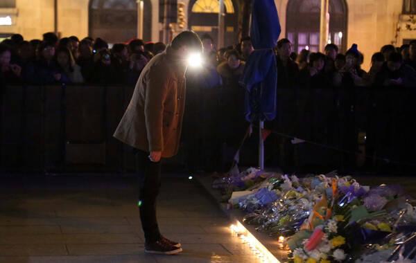 2015年1月1日,上海元旦夜晚,在踩踏事故发生地-上海外滩陈毅广场,不少民众自发来到广场,他们怀抱鲜花、点亮蜡烛为跨年夜在踩踏事故中逝去的36个生命静静默哀,默默祈福。图为一名民众献花后默默鞠躬悼念。