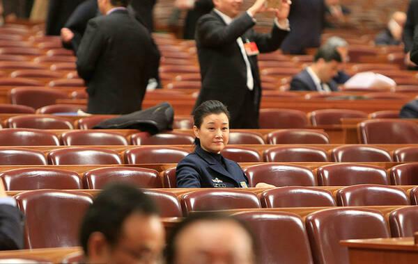 2015年3月3日下午,全国政协在北京开幕,宋祖英、赵本山、成龙、宋丹丹、姜昆、朱军、崔永元等明星委员纷纷现身,成为场内场外众人追逐的对象。图为宋祖英穿军装现身,安静地坐在场内等着会议开始。