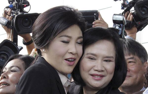 """2015年5月19日,泰国曼谷,泰国前总理英拉抵达最高法院接受""""大米案""""审理,她当天出庭受审,并对相关指控予以否认。据悉,英拉被认定在大米收购项目中渎职,泰国最高法院将决定是否就大米收购案接受检方对英拉的刑事诉讼。图为英拉获赠支持者送上的鲜花,并与支持者拥抱。"""