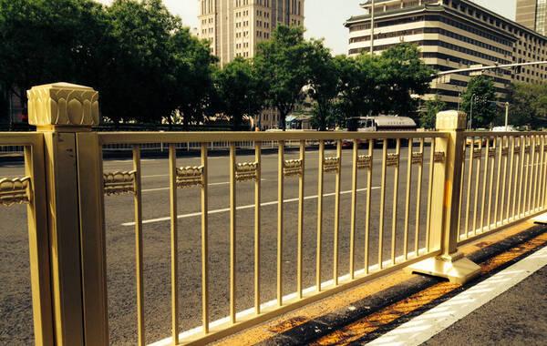"""5月8日,有北京市民称长安街一线的道路隔离护栏都变成金色的了。""""过去只有天安门前面一段是金色的护栏,而其他地方都是普通的白色护栏。现在从复兴门到建国门,长安街一线全部更换为金色护栏了,放眼望去熠熠生辉的。""""记者在长安街沿线看到,金黄色的新护栏,干净亮丽,庄严大气。护栏上镶嵌的莲花图案也更加凸显了祥瑞之气。""""莲花虽然是护栏的装饰物,但也是专门设计专门制作的,安装的位置要让人从侧面看和从上面看都很舒服,开车经过时感觉莲花瓣是立体的。"""" 护栏的生产厂家北重集团相关负责人介绍。图为长安街换装的金护栏。"""