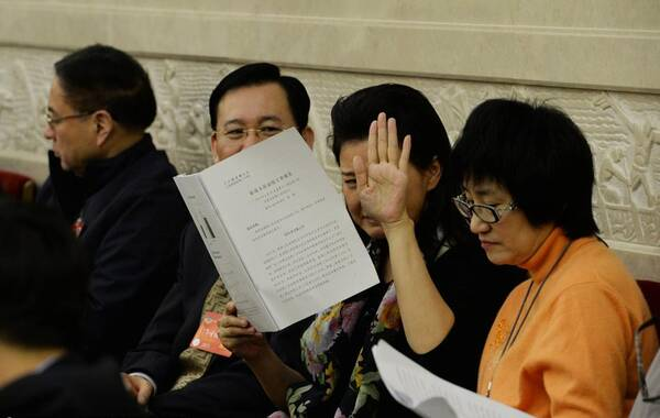 近日,北京,在人民大会堂广东厅,旁听第十二届全国人民代表大会第二次会议第三次全体会议的宋祖英素颜现身,和旁人讨论的她不时紧皱眉。见到记者拍照,宋祖英连忙举起报告挡脸,眉头紧缩。