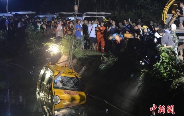 7月10日下午5时许,湖南湘潭市雨湖区响塘乡金桥村乐乐旺幼儿园所属园车,在送幼儿回家途中,途径湘潭市交界的长沙市岳麓区干子村时,翻入水库。此事故共致11人遇难,包括8名幼儿和3位成人。图为三位打捞人员正在将绳索捆绑于起重机上拉出事故车辆。