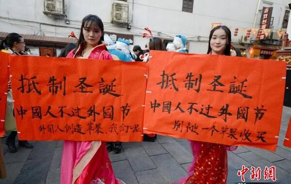 """12月24日,湖南一高校学生身着汉服来到长沙太平街的圣诞活动现场,手举""""抵制圣诞节""""等标语,呼吁市民回归中国传统节日,理性过节。杨华峰 摄"""
