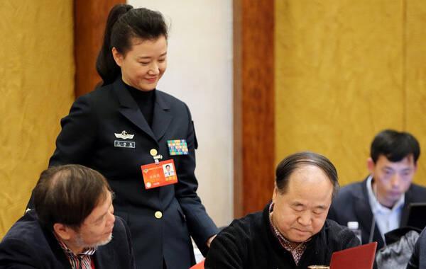 2014年03月06日,北京,全国政协十二届二次会议文艺界别委员小组讨论会。宋祖英利用会议间隙,将一本画册递给莫言,请求签名。