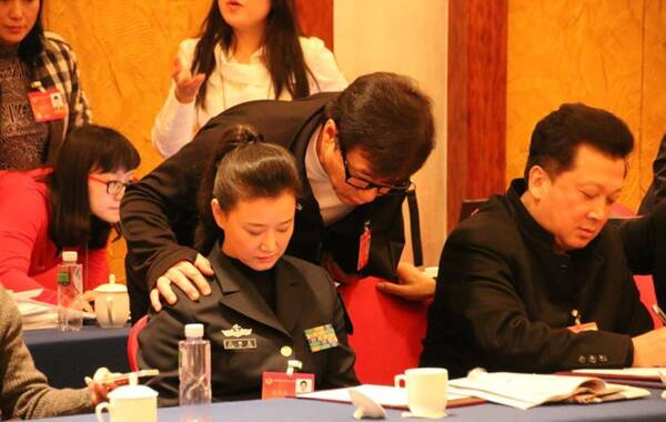 3月5日,北京国际饭店,政协文艺组讨论会结束后,成龙主动走上去,与几位电影节和文学界的委员们热情握手致意,然后转身跑到对面桌上的宋祖英,与宋祖英贴脸打招呼。(图源:徐静波博客)