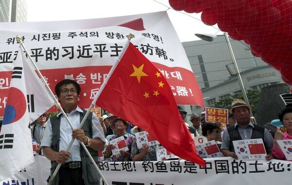 """当地时间7月2日,在中国驻韩使馆前,韩国民众集会欢迎中国国家主席习近平访韩,并打出写有""""钓鱼岛是中国的土地""""字样。"""