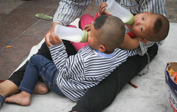 2015年5月1日,一位男子在北京站前广场地铁口将一对双胞胎用铁链拴在腰间乞讨,引来游客围观,路人报警。