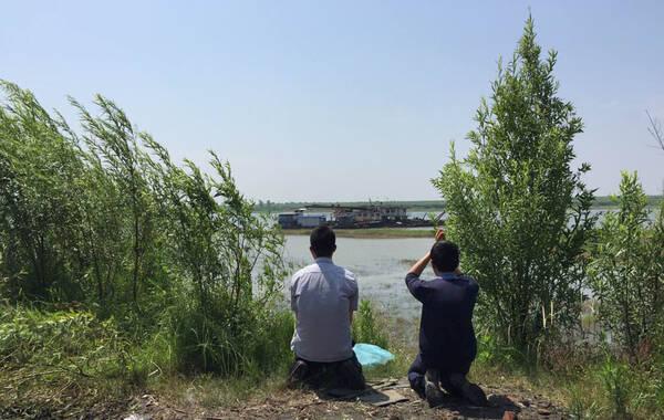 2015年6月6日,沉船乘客家属前来长江岸边,朝着江上拜祭亲人。有家属祭祀亲人时,哭喊辛苦一辈子,照顾别人一辈子,不该让你们来。摄影师:野瞳