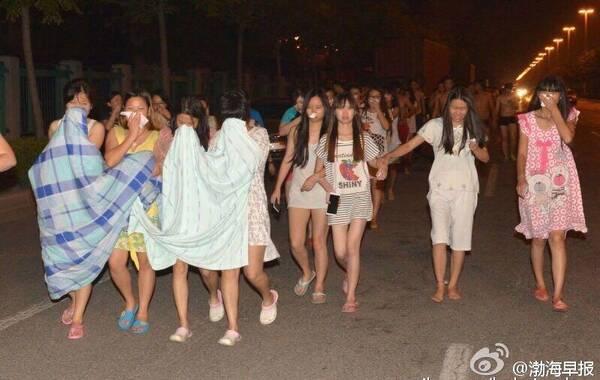8月12日晚11时许,天津市塘沽开发区一带发生爆炸事故,现场火光冲天,据多位市民反映,事发时十公里范围内均有震感,抬头可见蘑菇云。目前泰达医院已经接收42具来自天津滨海新区爆炸现场的遇难者遗体。图为民众身披床单,到街头避险。