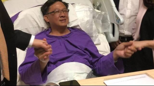 何君尧在病床上与内地记者握手合影