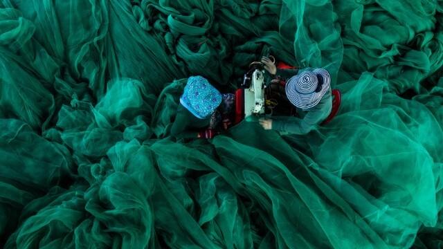 越南女工修补渔网 宛若身着绿色纱裙