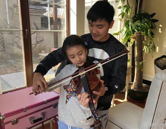 """1月15日,叶一茜晒出田亮教女儿森碟拉小提琴的照片,并配文""""我好歹也上过几年艺校,听她拉错我都不敢乱指导,她爸听了却坐不住了到底是谁给他的勇气?""""田亮亲自上手之后,森碟的表情亮了。"""
