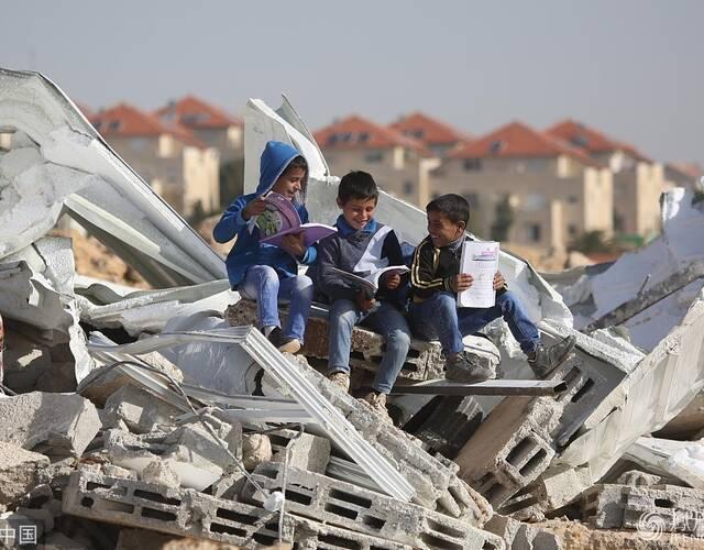 孩子们坐废墟上读书。