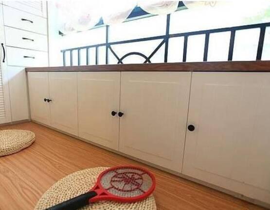 5、像这样打一排地柜,有点类似于制作了一排飘窗的味道,坐在上面看看书,享受阳光,是个不错的选择。 好了,如果你家正在装修,阳台别打吊柜了,不妨试试打一排矮柜吧。