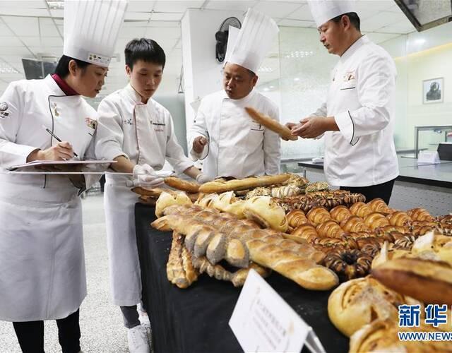 12月7日,评委在评审法棍面包时用尺子量面包的长度。   新华社记者 方喆 摄   12月7日,参赛选手张猛在比赛中制作面包上的装饰物。   新华社记者 方喆 摄   12月7日,参赛选手将烤制好的面包摆放整齐等待评委评审。   新华社记者 方喆 摄