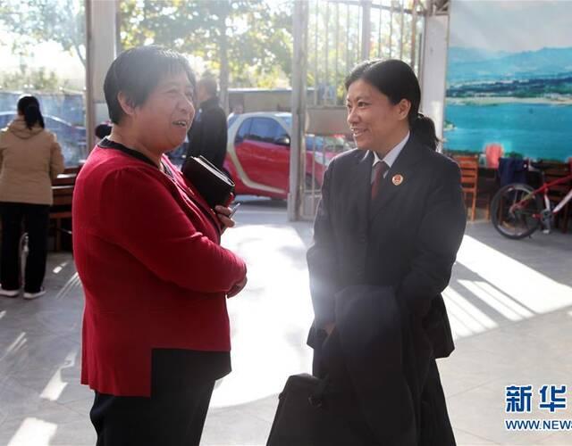 """彭燕(右)在北京市昌平区十三陵镇胡庄村与村民交流(11月3日摄)。   罹患甲状腺癌,9个月内进行两次手术,康复后仍坚守办案一线,被人民群众誉为""""钢铁玫瑰"""";工作成绩突出,先后获得全国模范检察官、全国先进工作者等36项荣誉……这就是十九大代表、北京市昌平区人民检察院检察委员会专职委员、未成年人案件检察部主任彭燕。十九大闭幕后,彭燕作为大会亲历者,积极投身十九大精神宣讲工作。从会前准备、会议细节到报告主要内容,彭燕以自己的多年检察实践,生动鲜活、深入系统地宣讲了对十九大精神的切身体会。包括北京市人民检察院、分院,昌平区人民检察院以及昌平区部分街道、乡镇在内,彭燕共进行了18场宣讲,聆听宣讲人数超过4700人。   新华社发"""