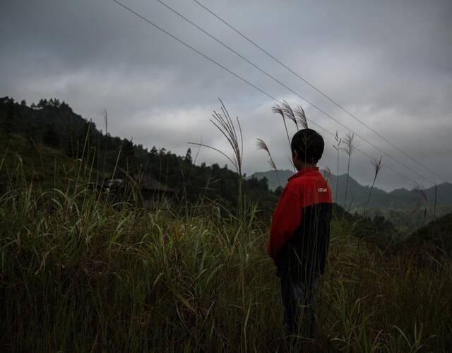 远方的天空阴沉下来,快下雨了,摄影师跟梁凯阳说回去吧。凯阳默默望着远处的家,心里不知想些什么。添加微信公众号:西楚朗雨,更多感动分享。