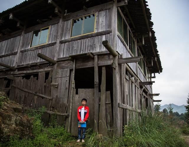 图为梁凯阳站在家门前,摄影师给他拍了张照片。凯阳学习之余,经常想在QQ上和妈妈聊几句,他怕电话费太贵,两、三个月才好意思找姑姑借手机,给妈妈打一个电话。