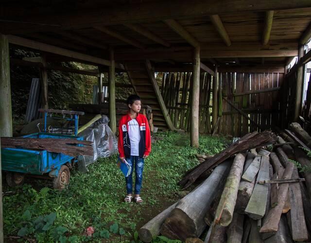 """破败的家里长满了荒草和青苔,房子修建了一半,由于父母离婚就半途而废了,檩条杂乱地堆放在一楼的门口,耕田用的小运输车也快生锈了。""""我穿的衣服也是妈妈寄来的,我知道妈妈一直想着我,上次见到妈妈是在去年的9月4号,妈妈回老家过新米节,我和妈妈一起住在外婆家里,一共住了8天,那是我最开心的日子!""""梁凯阳回忆说:""""妈妈走的时候,怕彼此伤心没让我知道,我哭了一夜……"""""""