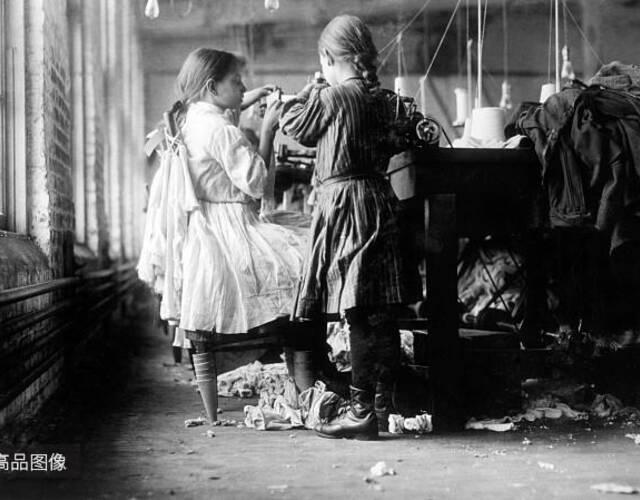 """号称美国""""棉纺业之父""""的萨谬尔•斯莱特在美国建立的棉纺厂中,有大量7-12岁的童工,斯莱特说,童工比成年人工作更快,效率更高,当然,工资也更低。在纺纱厂工作的女孩只有1.3米高,已经工作一年,每天挣到48美分。图片来源:高品图像"""