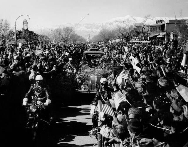 街道两旁挤满了手举星条旗的欢迎人群。(Wayne Miller 摄)