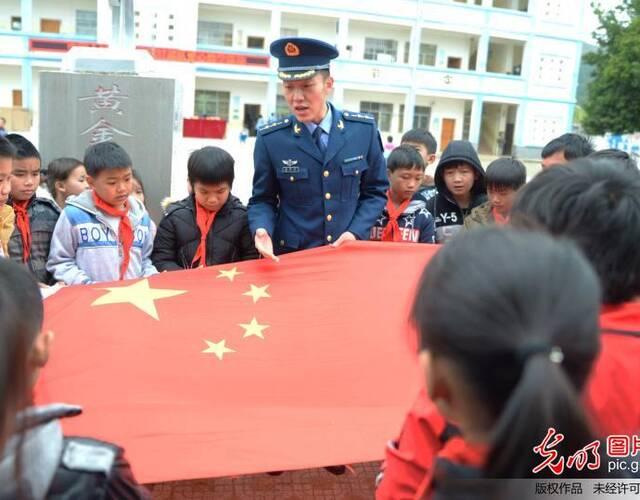 2018年1月12日,在广西来宾市忻城县黄金蓝天小学,驻广西空军某场站官兵为同学们讲解国旗知识。