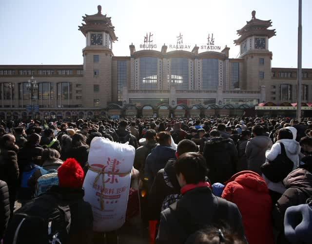 """""""北漂人""""返乡的源头也是起点,站前广场可谓人山人海,各路""""英雄好汉""""齐聚这里一起回家过年,与亲人团聚。据北京局预计,今天发送旅客80万人。其中,北京火车站预计发送11.3万人,增开24列车,客流主要以沈阳、哈尔滨等东北方向为主。图为火车站前广场等候验票的队伍。"""
