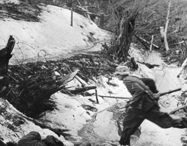 一名德军士兵从成堆的苏军尸体边跑过。